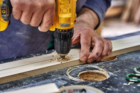 Joinery. Carpenter drills the holes. Woodworking and carpentry production. Furniture manufacture. Close-up