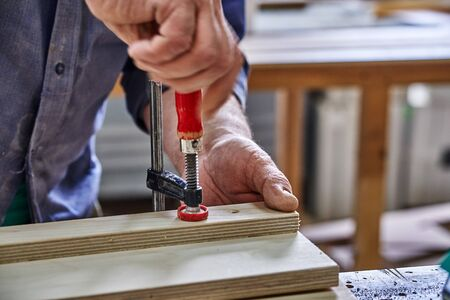 Joinery. Carpenter clamping plywood parts. Woodworking and carpentry production. Furniture manufacture. Close-up Reklamní fotografie