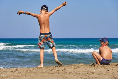 Back view of kids in shorts and caps with torso spending time together and having fun on seashore by water on sunny day