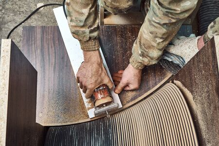 Joinery. Unrecognizable craftsman using professional tool for woodwork while making round coffee table in workshop