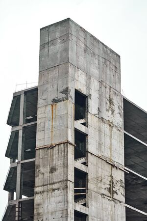 Monolithic construction of a multi-storey apartment building. Construction site. Unfinished construction and reinforced concrete house frame