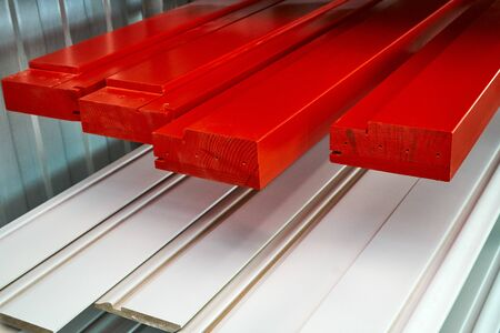 Painted furniture elements in the spray booth. Red enamel. Furniture manufacture.. Wooden furniture manufacturing process