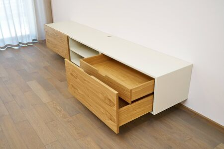 Contemporary floating media cabinet in living room. Wooden wall mounted cabinet with open drawers