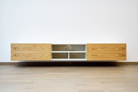 Contemporary floating media cabinet in living room. Wooden wall mounted cabinet