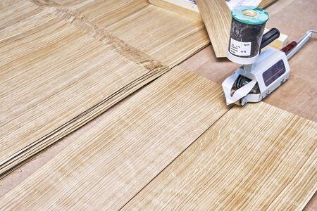 Oak veneer. Oak texture. Veneer splicing process with veneer hand splicer in woodshop. Close-up