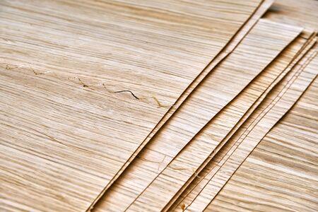 Oak veneer. Oak texture. Spliced oak veneer on the table in the workshop. Close-up