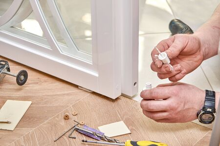 Sliding glass doors repair. Worker install end cap. White sliding glass doors with overlays decor. Close-up Stockfoto