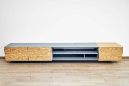 Contemporary floating media cabinet in living room. Wall mounted wooden cabinet