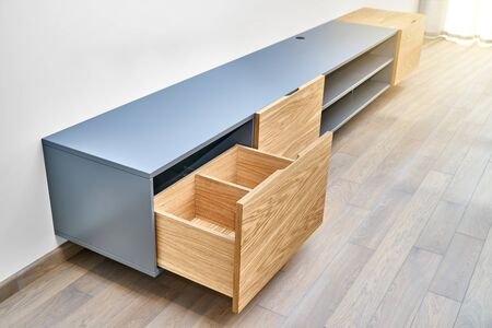 Contemporary floating media cabinet in living room. Wall mounted wooden cabinet with open drawers