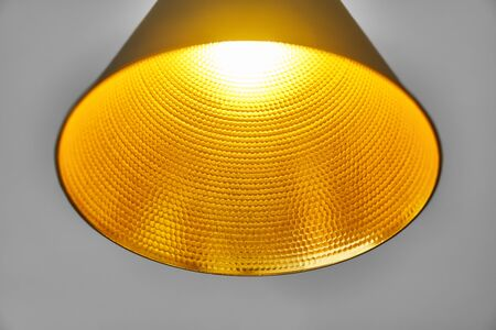 Gold embossed lampshade. Round yellow lamp on grey background. Close-up