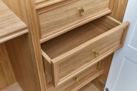 Wooden drawers with golden handles close-up. Wooden filling of wardrobe. Wooden wardrobe with white lacquered cabinet doors