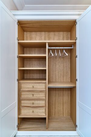 Opened white wardrobe with wooden drawers and shelves. Wooden filling of wardrobe and white clothes hangers. Wooden wardrobe with white lacquered cabinet doors