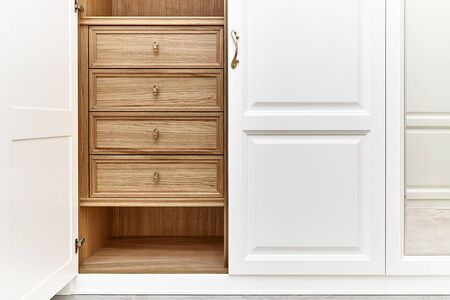 Opened white wardrobe with wooden drawers and shelves. Wooden filling of wardrobe. Wooden wardrobe with white lacquered cabinet doors 免版税图像