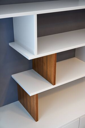 Modern bookcase. White and wooden bookshelves in contemporary interior. White enamel wooden bookcase close-up