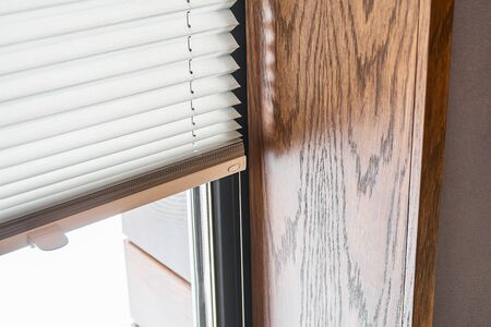 Oak veneer window slopes. Wooden slopes on the window. Window with pleated shades. Close-up
