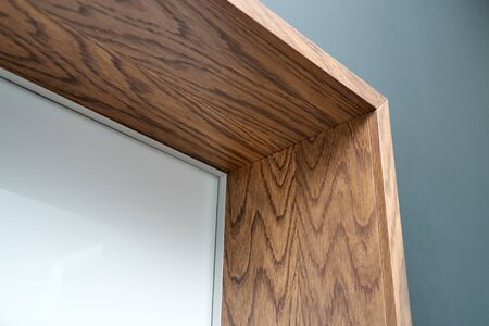 Aluminum frame hidden door with wooden slopes and wooden architraves. Close-up