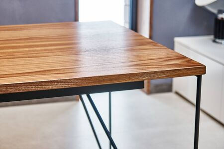 Wooden office desk . Walnut veneer desk with metal base. Close-up 免版税图像