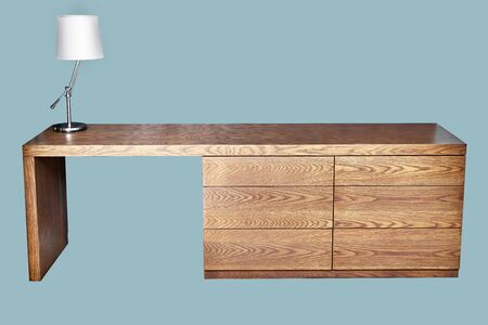 Oak veneer dresser table. Wooden dresser table with lamp on green background