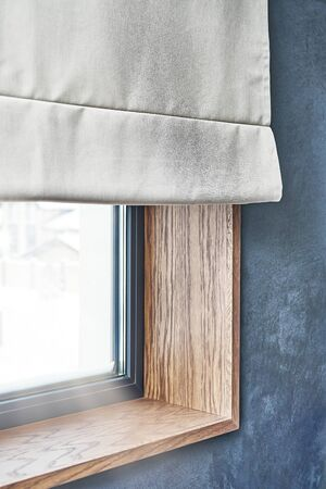 Oak veneer window slopes. Wooden slopes on the window. Window with roman shades. Close-up 免版税图像