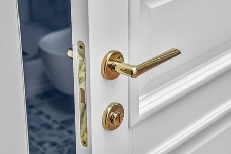 Classic style white door. Opened white door to the bathroom. Classic white door with golden handle. Close-up