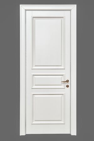 Classic style white door. White interior door with golden handle isolated on gray background. Furniture manufacture.