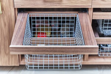 Storage organization. Metal mesh basket in wooden drawer in food storage room. Close-up 免版税图像