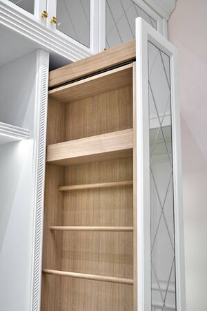 White wardrobe with mirror doors. Vertical pull-out wooden cabinet in the dressing room. Classic furniture close-up 免版税图像