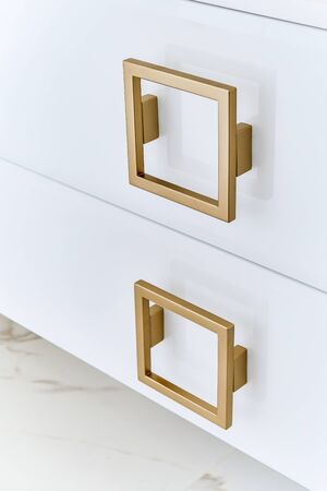 Square gold handles on a gloss cabinet doors of bathroom vanity. Close-up