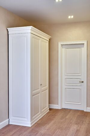 Classic wardrobe and interior door in beige interior. Classic furniture. Furniture manufacture