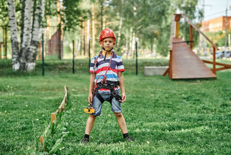 Full body boy in climbing equipment and helmet standing on grass and looking at camera on summer day in rope park