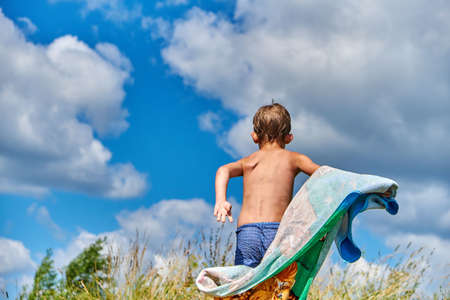 Back view of little wet boy with towel running on grass against cloudy sky on sunny day in countryside