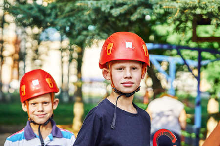 Two boys in climbing equipment and helmet standing on grass and looking at camera on summer day in park. No logo
