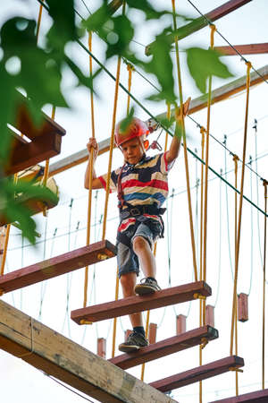 From below boy in helmet and climbing equipment walking on the ropes against sky while spending time in rope park 免版税图像