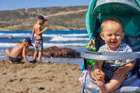 Happy little male infant enjoying sunlight in stroller while brothers playing on seashore in summertime