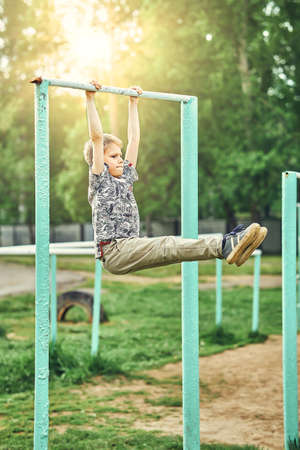 Full body side view of focused preteen boy in casual clothes doing exercises on metal bar while spending summer day on sports ground in park