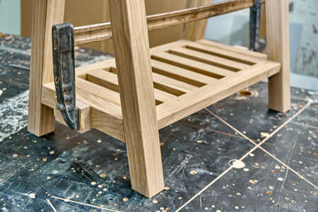 Joinery. Gluing and clamping wooden table leg. Wooden furniture manufacturing process. Furniture manufacture. Close-up