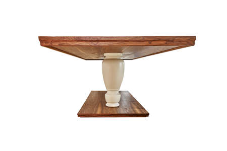 Dinner table made of solid walnut wood on massive legs isolated against white background