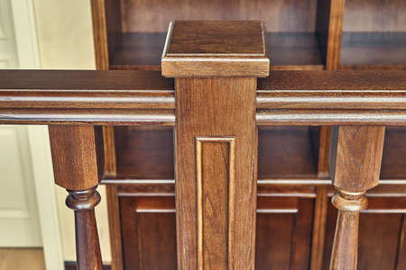 Perspective view of detail of ornate wooden railing in contemporary house with classic interior