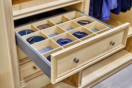 Wooden wardrobe. Open drawer with men's belts close-up 版權商用圖片