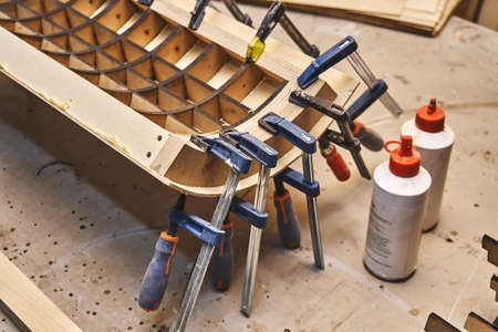Joinery. Plywood bending process close-up. Gluing and clamping bend wooden panel. Bend furniture manufacture Banco de Imagens
