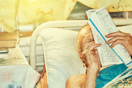 Senior man doing crossword puzzle lying in bed by lamp light