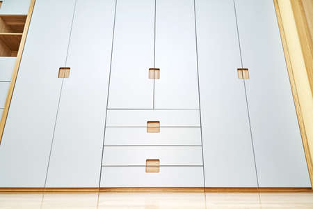 Modern wooden wardrobe with flat finger pull wardrobe doors. Oak veneered plywood cabinets with light gray painted cabinet doors. Modern furniture Stockfoto
