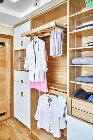 Internal details of the wooden wardrobe with slide out rack for coathangers. Modern wardrobe with clothes hanging on slide out racks and folded on the shelves. Modern furniture