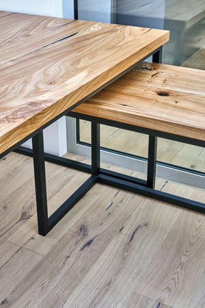 Live edge elm gaming desk countertop with metal base in a modern home office. Fragment of the desk