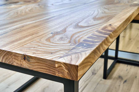 Live edge elm gaming desk countertop with metal base in a modern home office. Details close-up