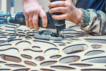 Decorative partition wall manufacturing process. Carpenter cuts holes in MDF using a jigsaw. Decorative partition wall with floral pattern.