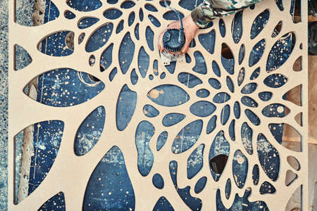 Decorative partition wall manufacturing process. Carpenter milling holes in MDF with a hand electric router machine. Decorative partition wall with floral pattern.