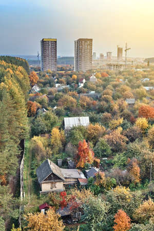 Contemporary highrise city dwelling buildings annex territory of neat summer cottages among colorful autumn trees at sunset