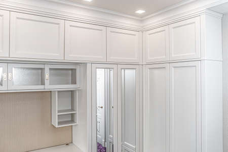 Classical style corner wardrobe with mirrors on a bright purple carpet in a bright room