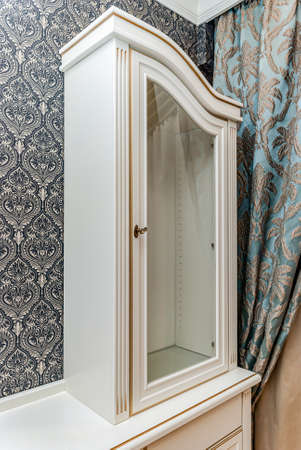 Classical style white showcase with glass doors and gilding on the background of black and white wallpaper with floral pattern